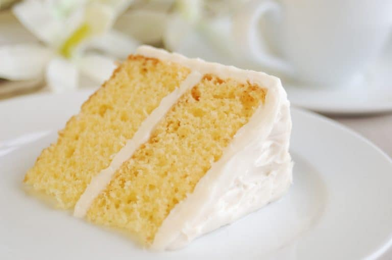 yellow cake with vanilla frosting on elegant table.