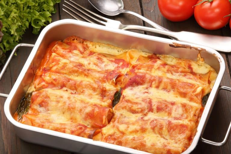 Cannelloni baked in a roasting pan on a wooden background