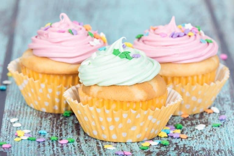 Pastel cupcakes with sprinkles on blue vintage background