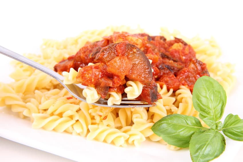 Fusilli pasta with pork & eggplant sauce, being eaten with a fork