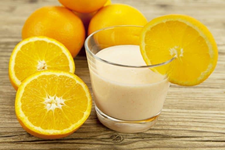 Frischer tropischer Joghurt mit Orangen auf einem Brett
